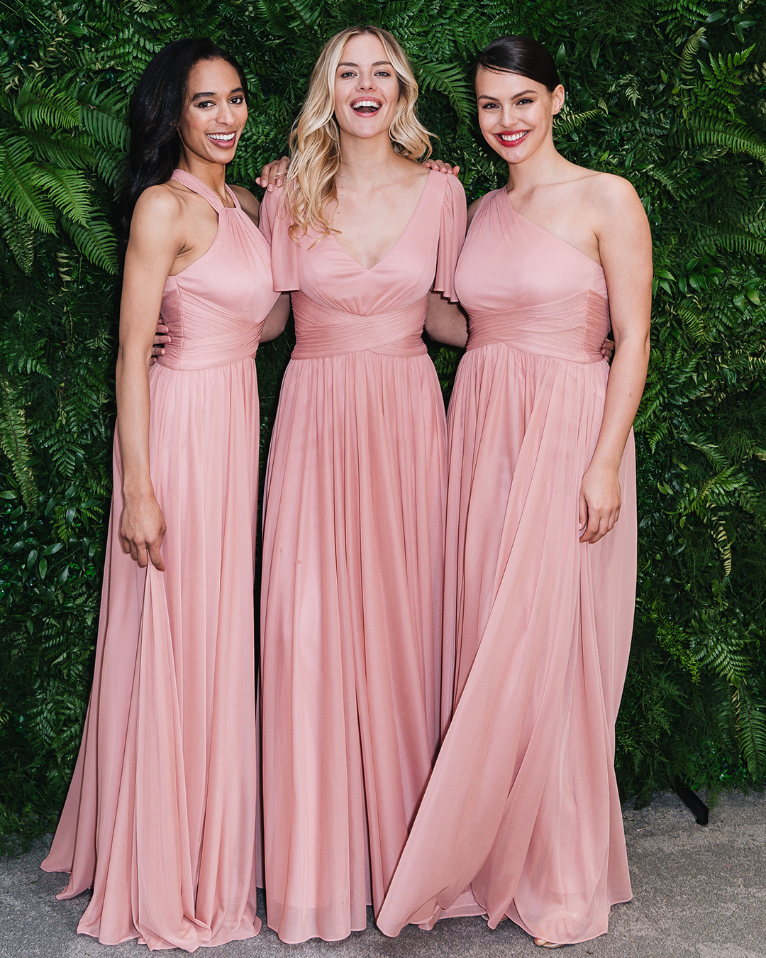 Three women in long coral bridesmaid dresses in front of greenery wall
