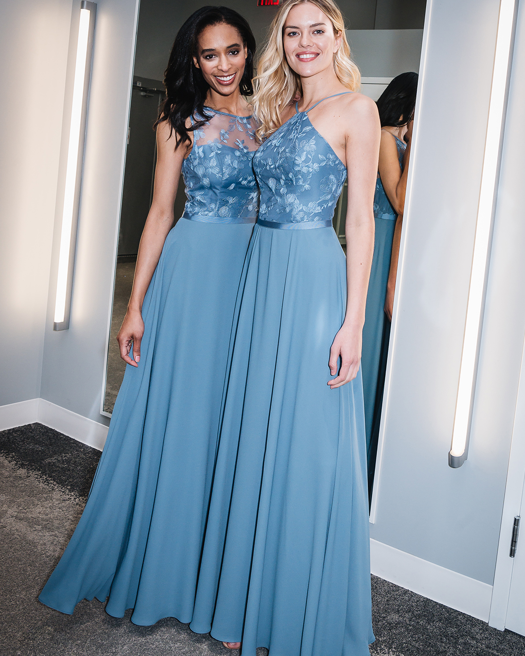 Two women in bridal shop in long blue bridesmaid dresses with embroidered bodice