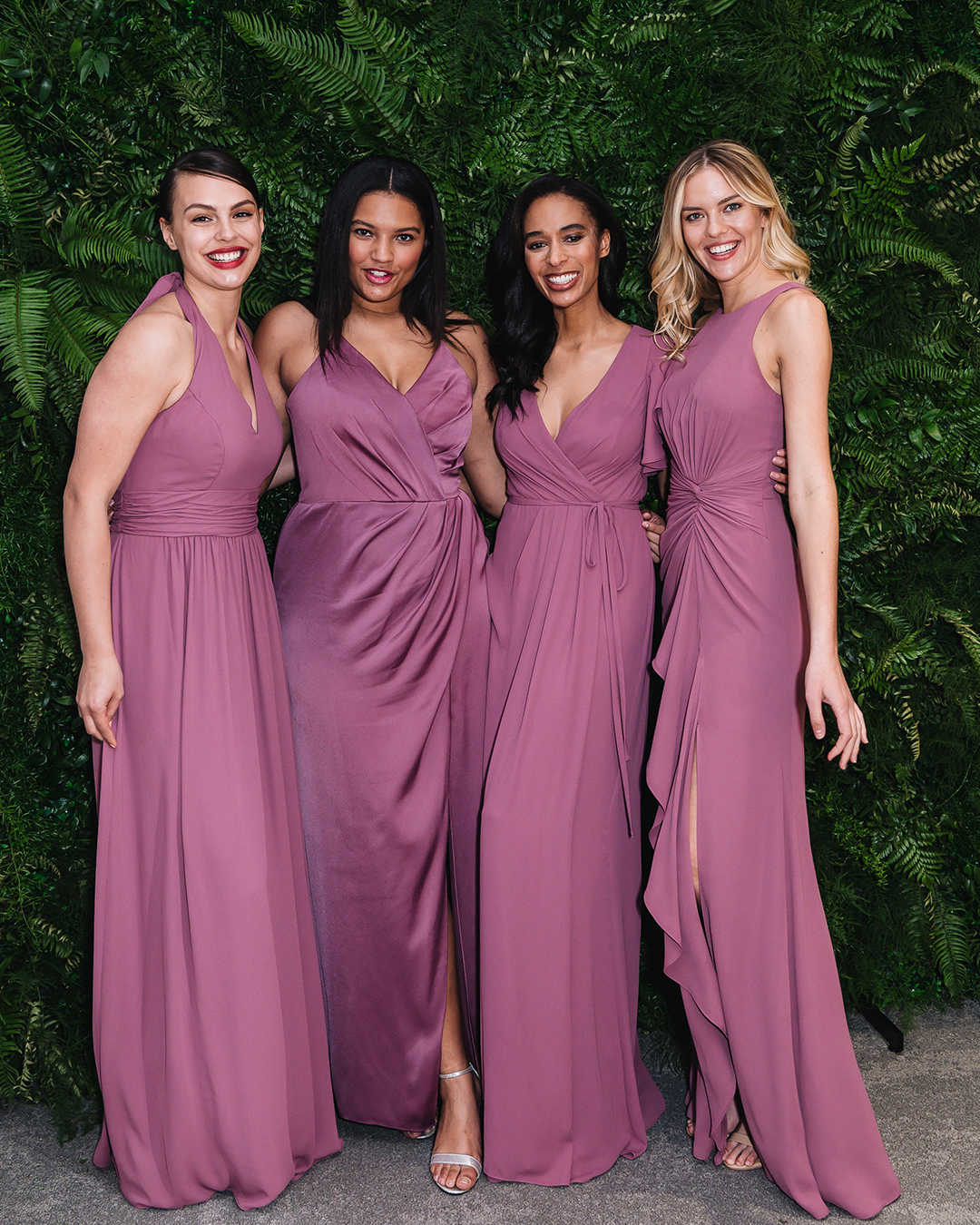 Four women in long wine colored bridesmaid dresses in front of greenery wall