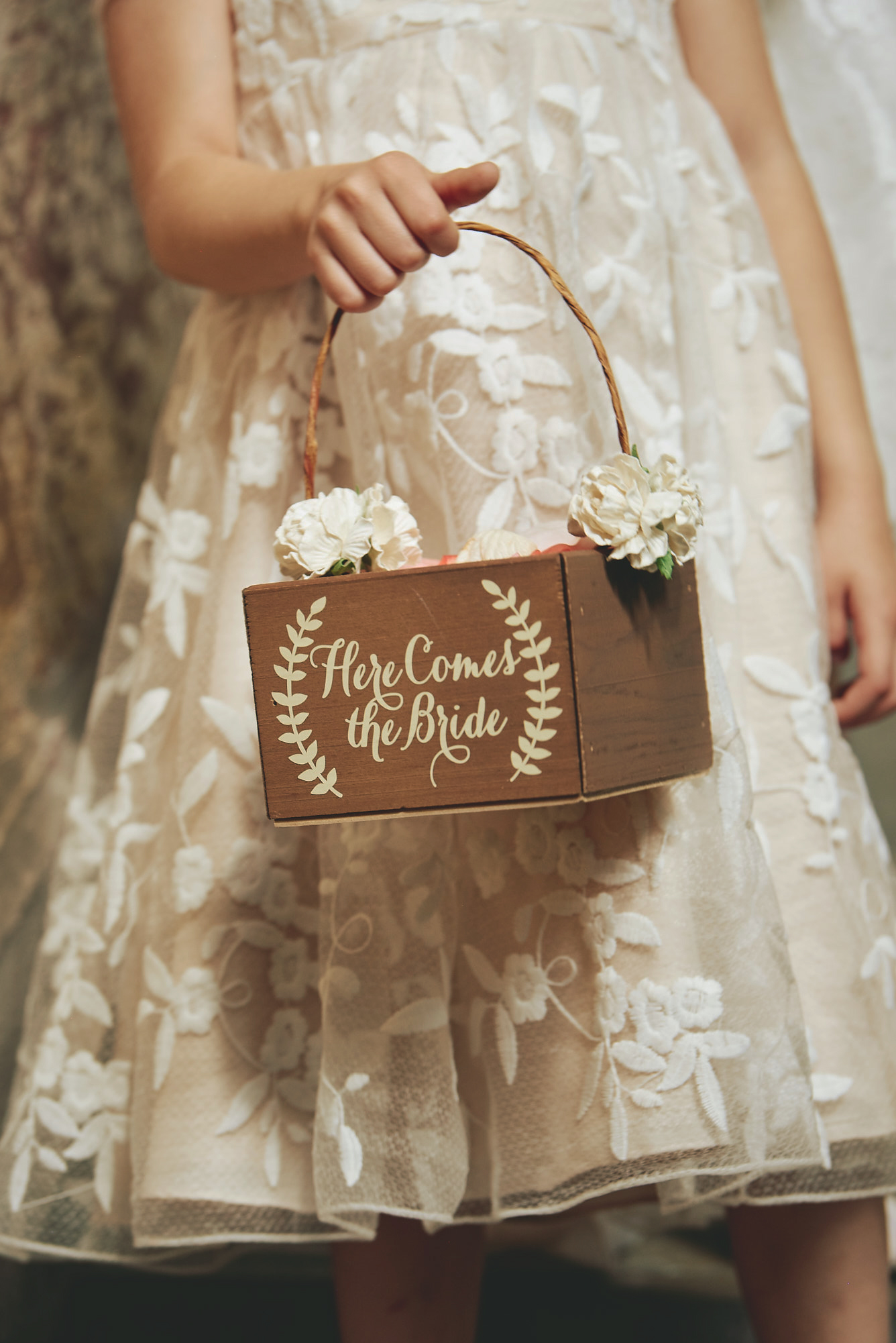 Flower girl in a lace dress holding a wooden basket with 'Here Comes the Bride' written on it