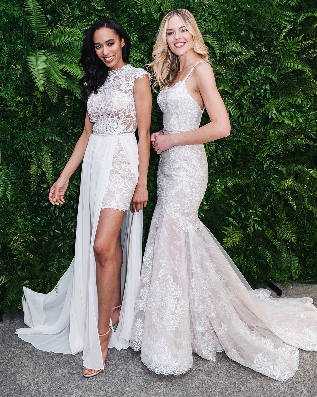 Two women in front of greenery in white lace wedding dresses