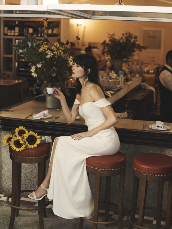 Bride sitting on stool in cafe wearing a draped off-the-should sheath wedding dress