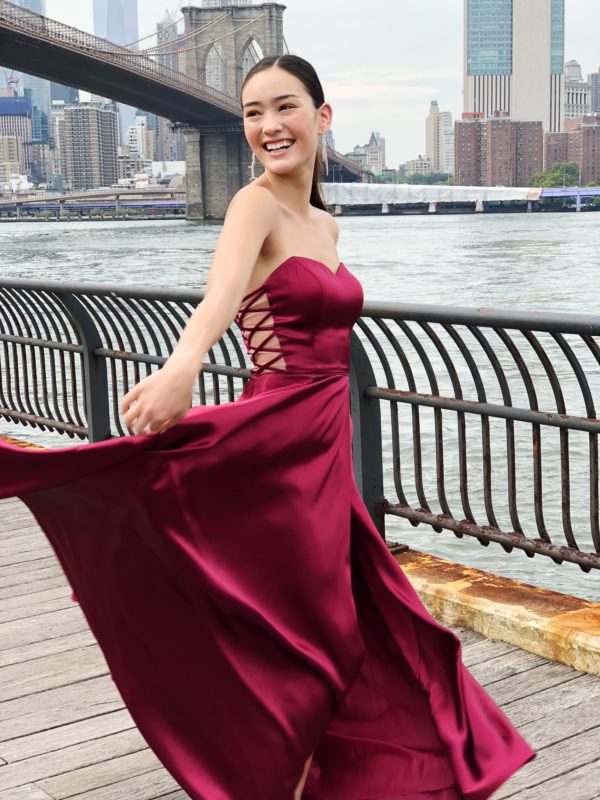 Girl in prom dress dancing on boardwalk at Brooklyn Bridge Park