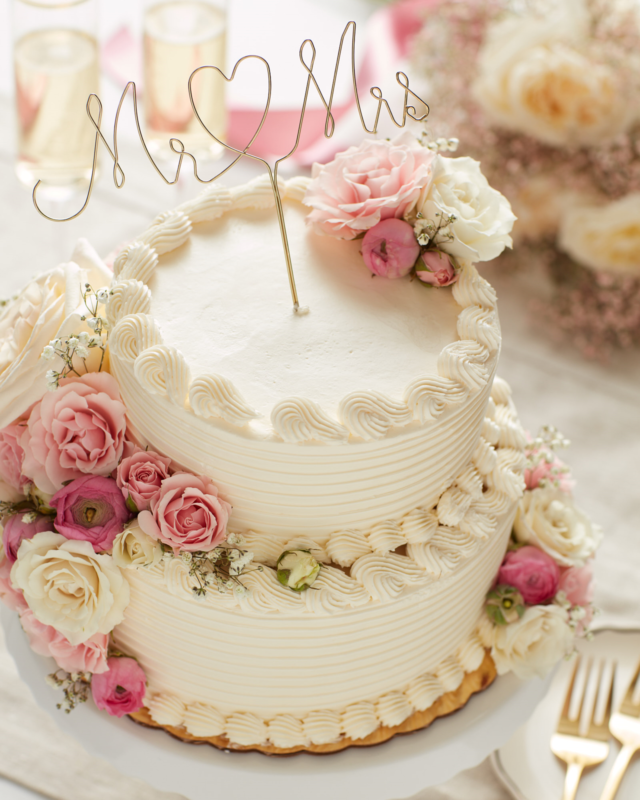 White two-tier wedding cake with pink and white flowers and a Mr and Mrs wire script with heart cake topper