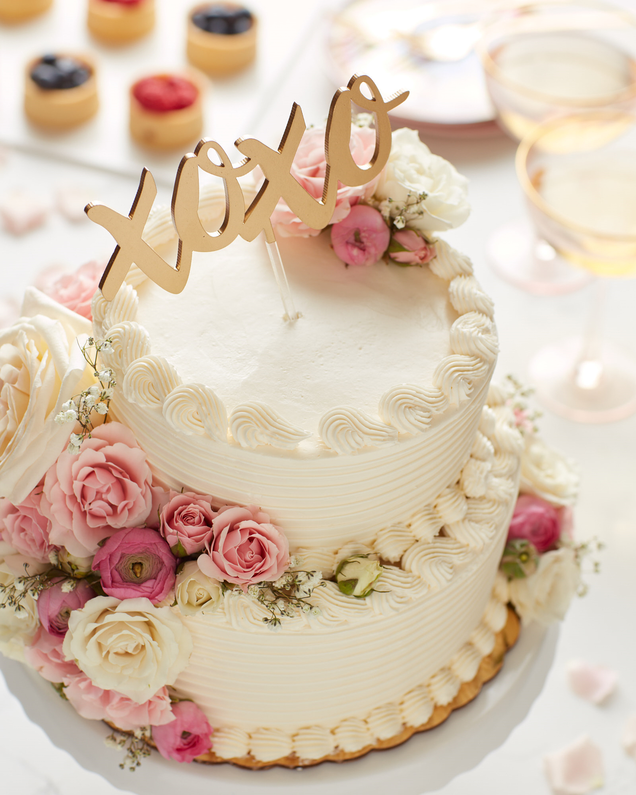 White two-tier wedding cake with pink and white flowers and a XOXO cake topper