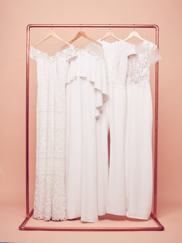 Bohemian wedding dresses hanging on a rack by Tadashi Shoji at David's Bridal