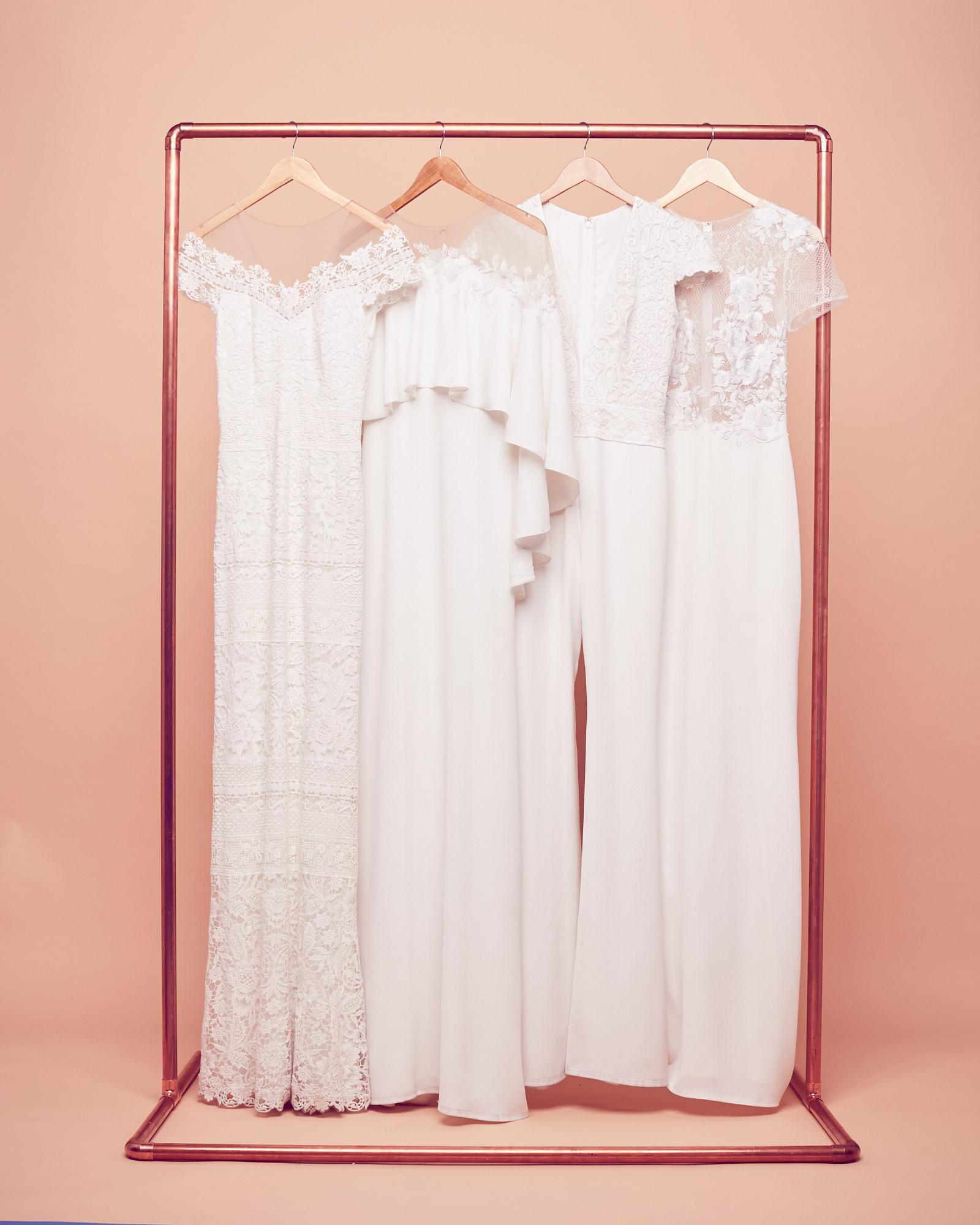 Bohemian wedding dresses hanging on a rack by Tadashi Shoji at David's Bridal