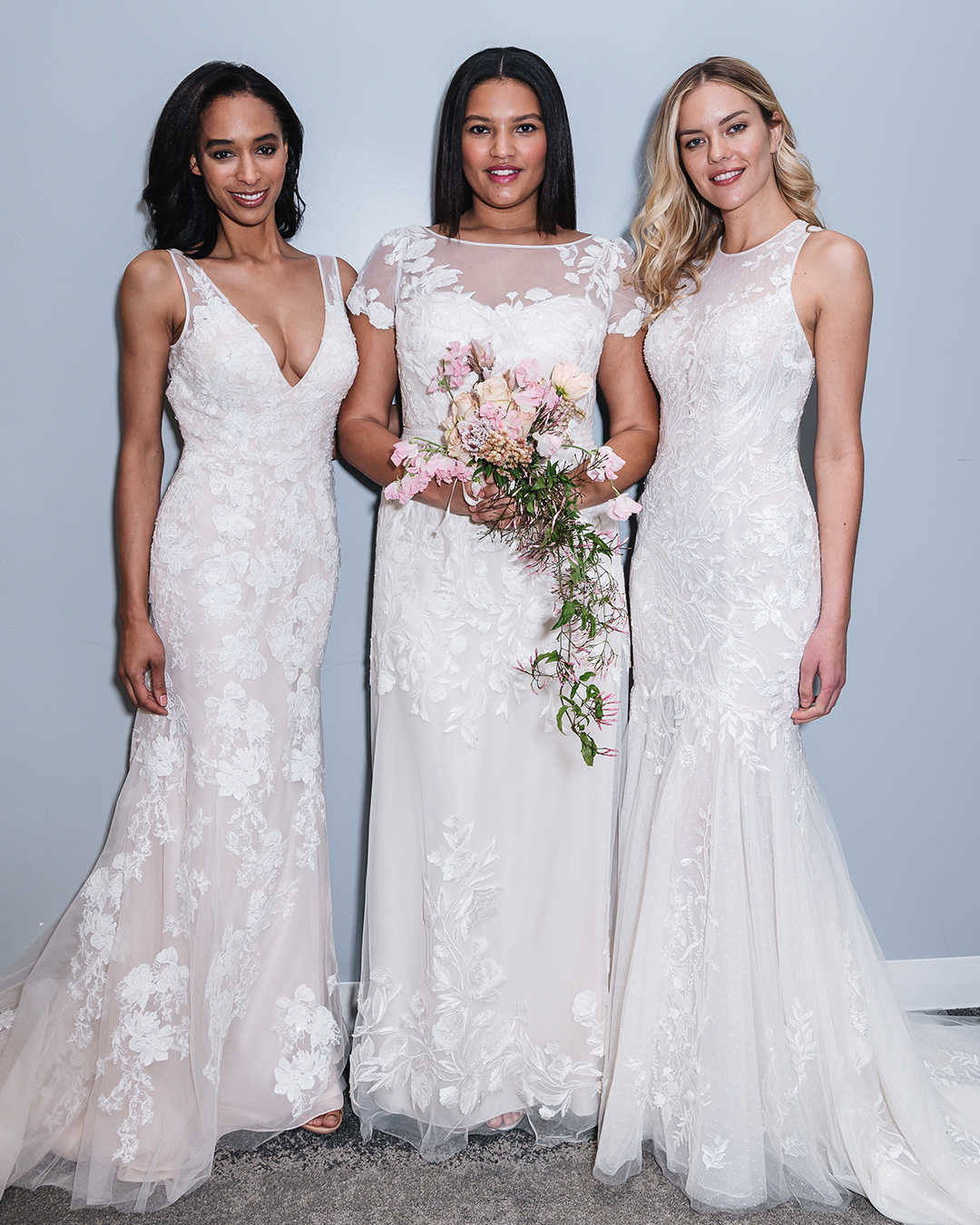 Three women in bridal store in lace wedding dresses