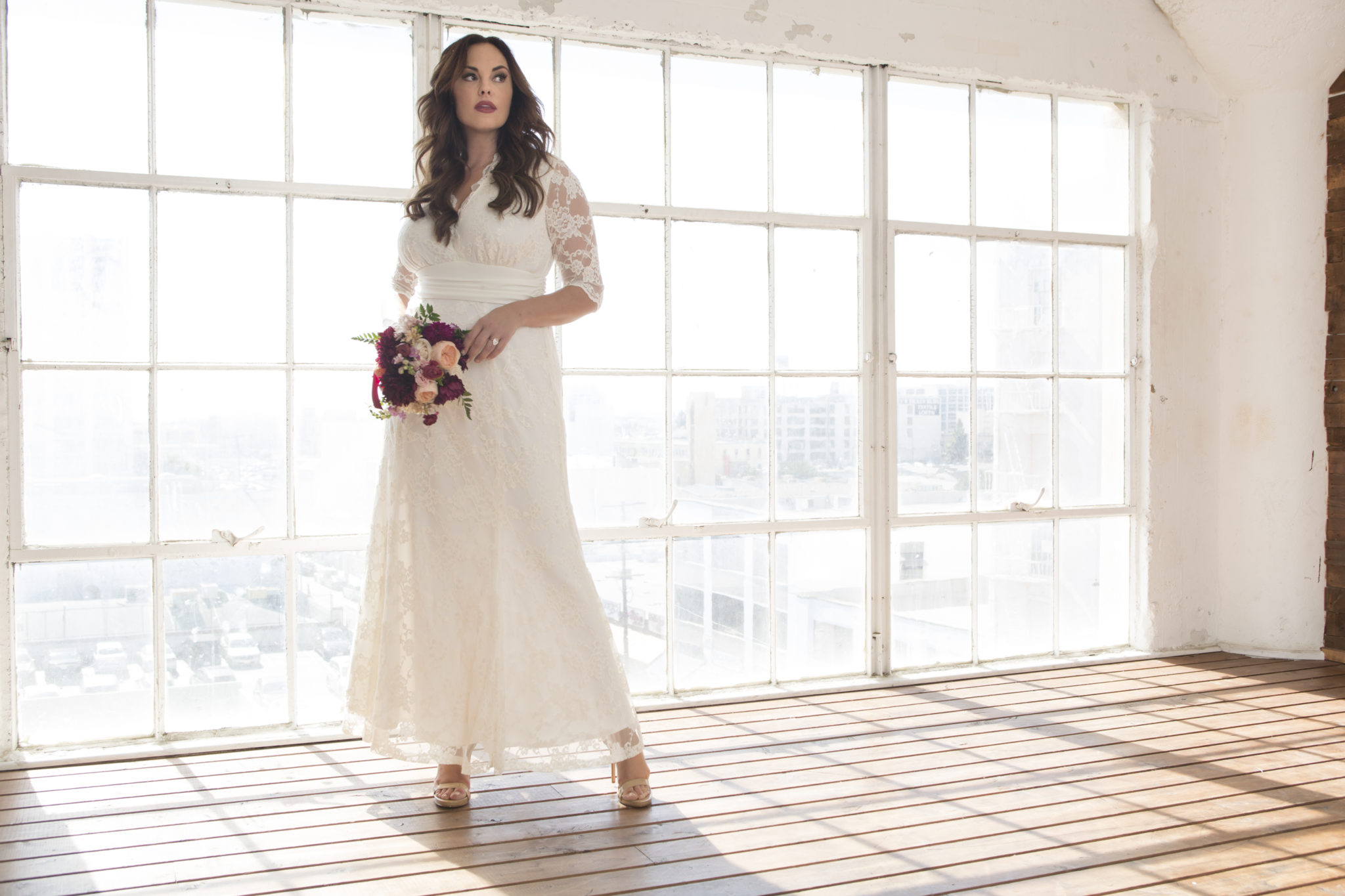 Bride in V-neck lace wedding dress with 3/4 sleeves against a wall of windows
