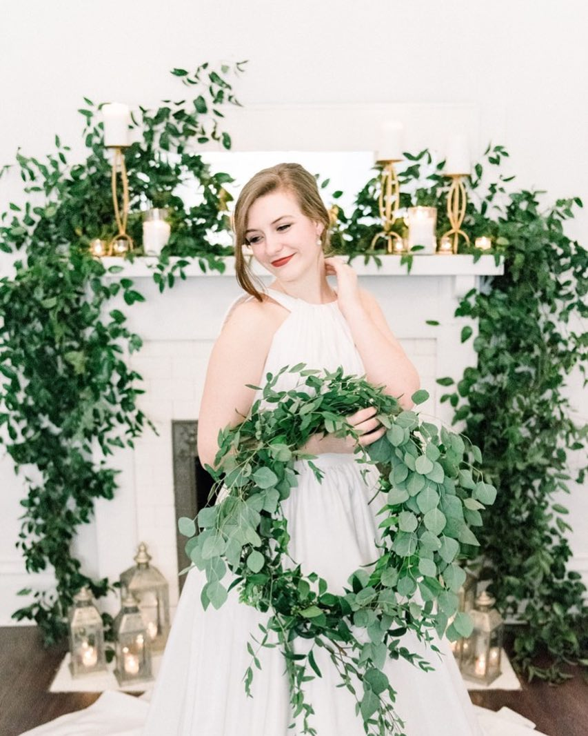 Bride in white dress holding greenery wreath or hoop bouquet | Nontraditional Wedding Bouquet Ideas