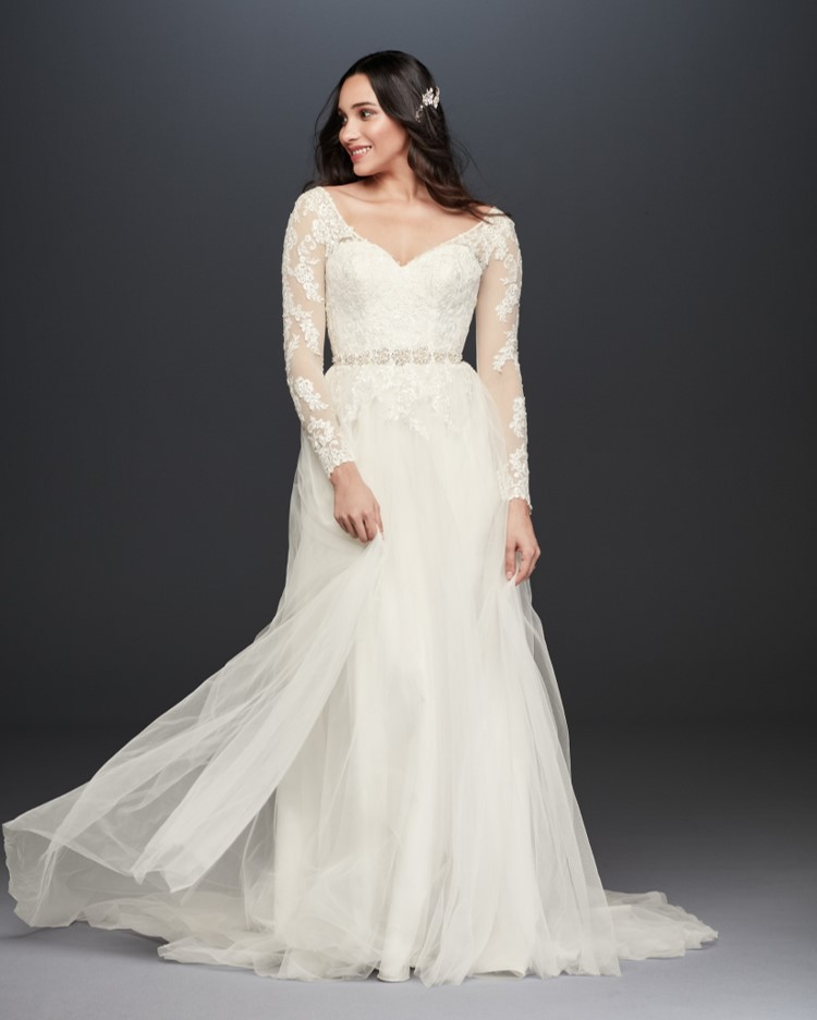 Bride in long sleeve lace ball gown wedding dress from David's Bridal's affordable wedding dresses assortment