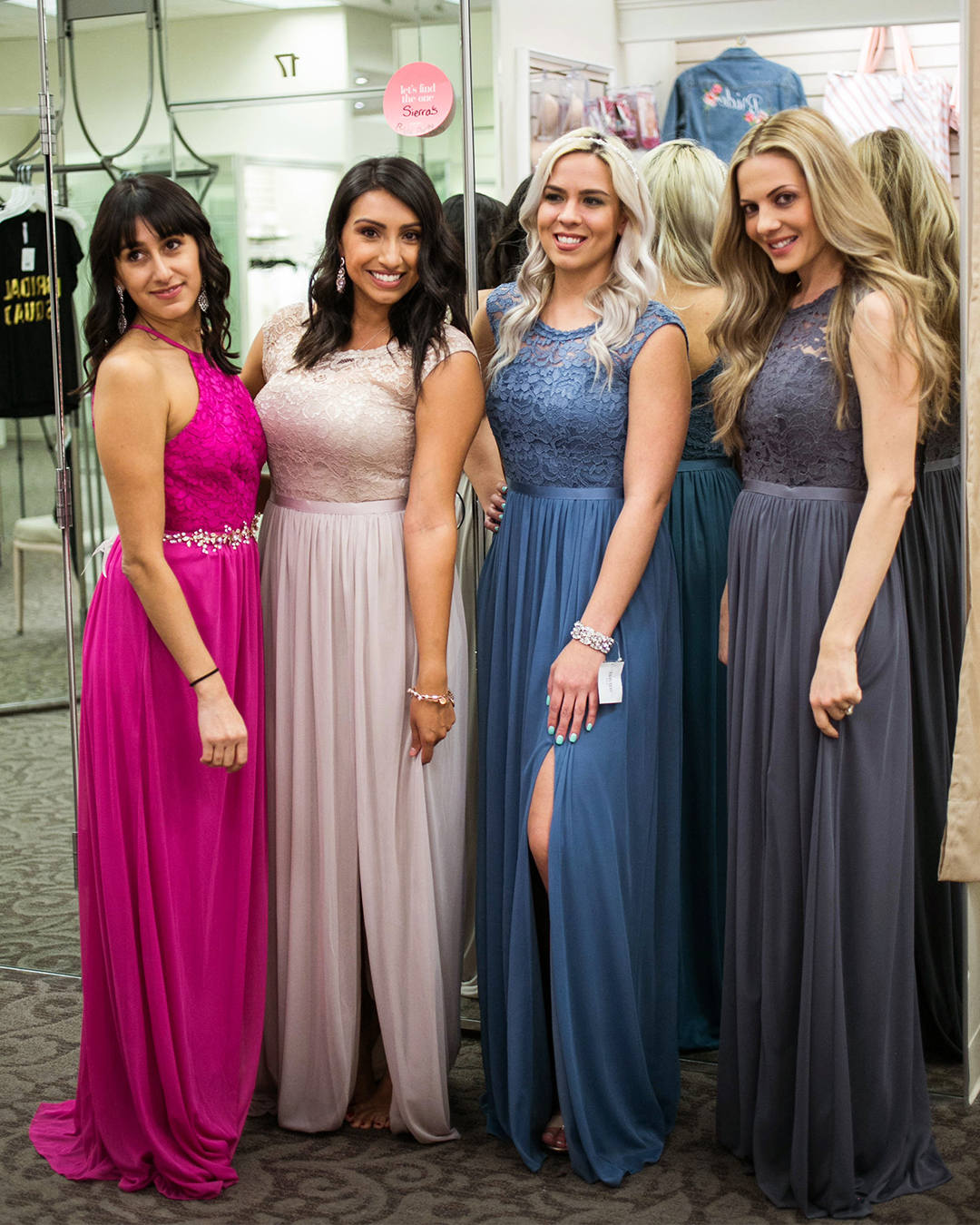 Four bridesmaids in long lace dresses shopping in David's Bridal store