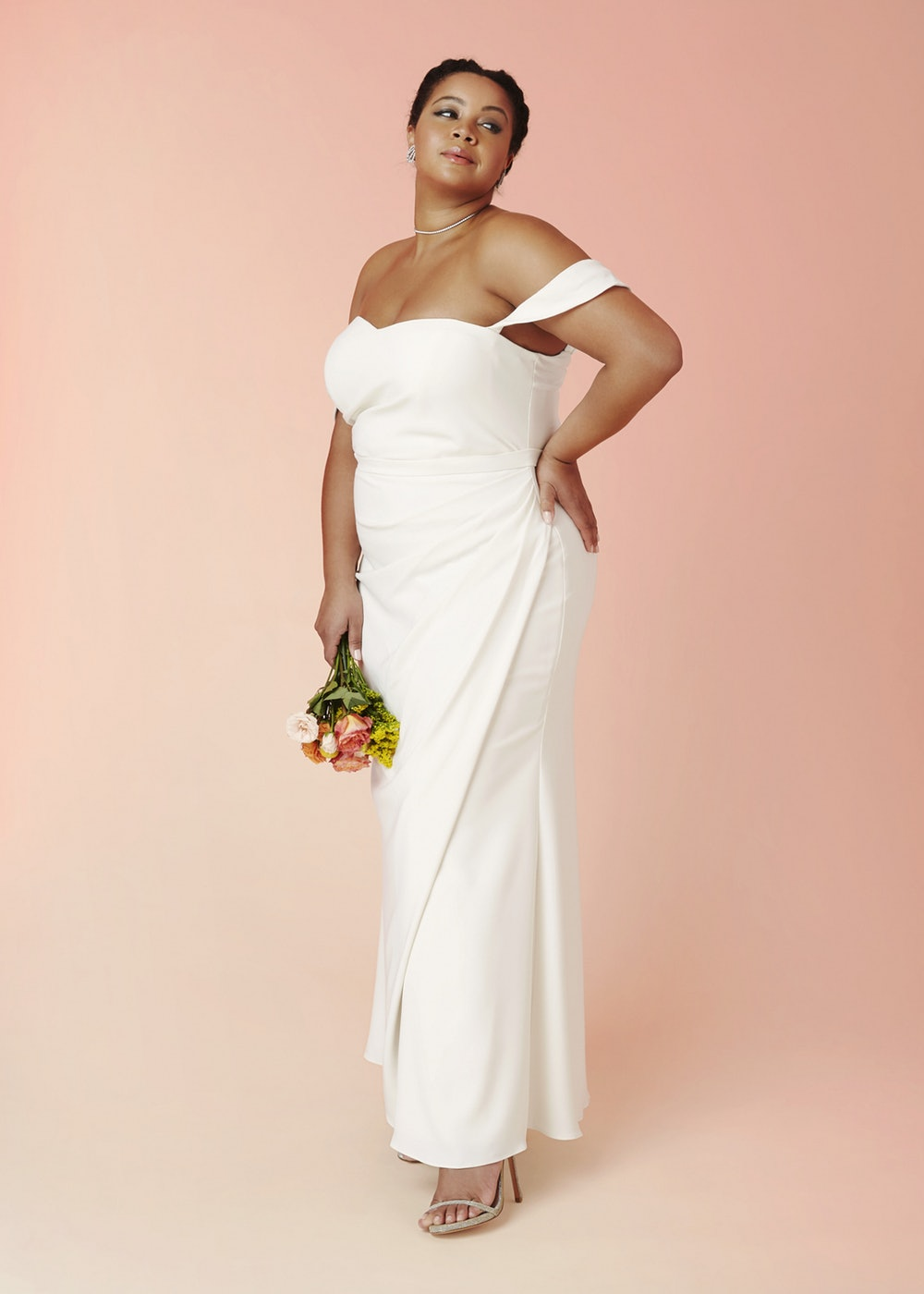 Plus size bride in a draped off-the-shoulder crepe sheath wedding dress