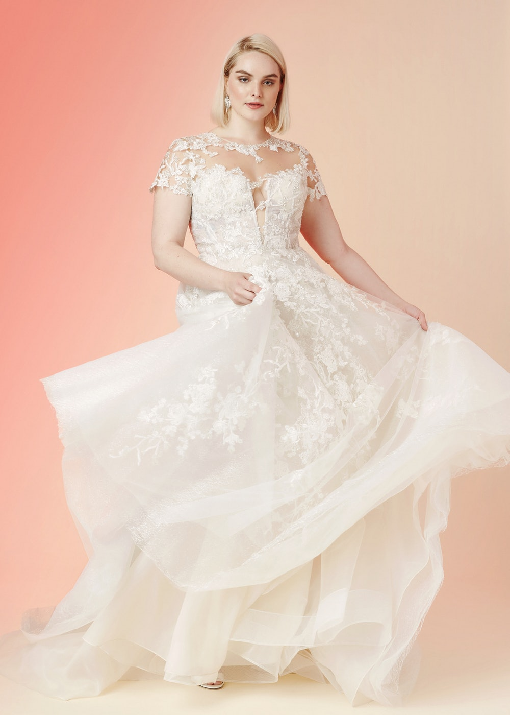 Plus size bride in a cap sleeve lace illusion wedding dress