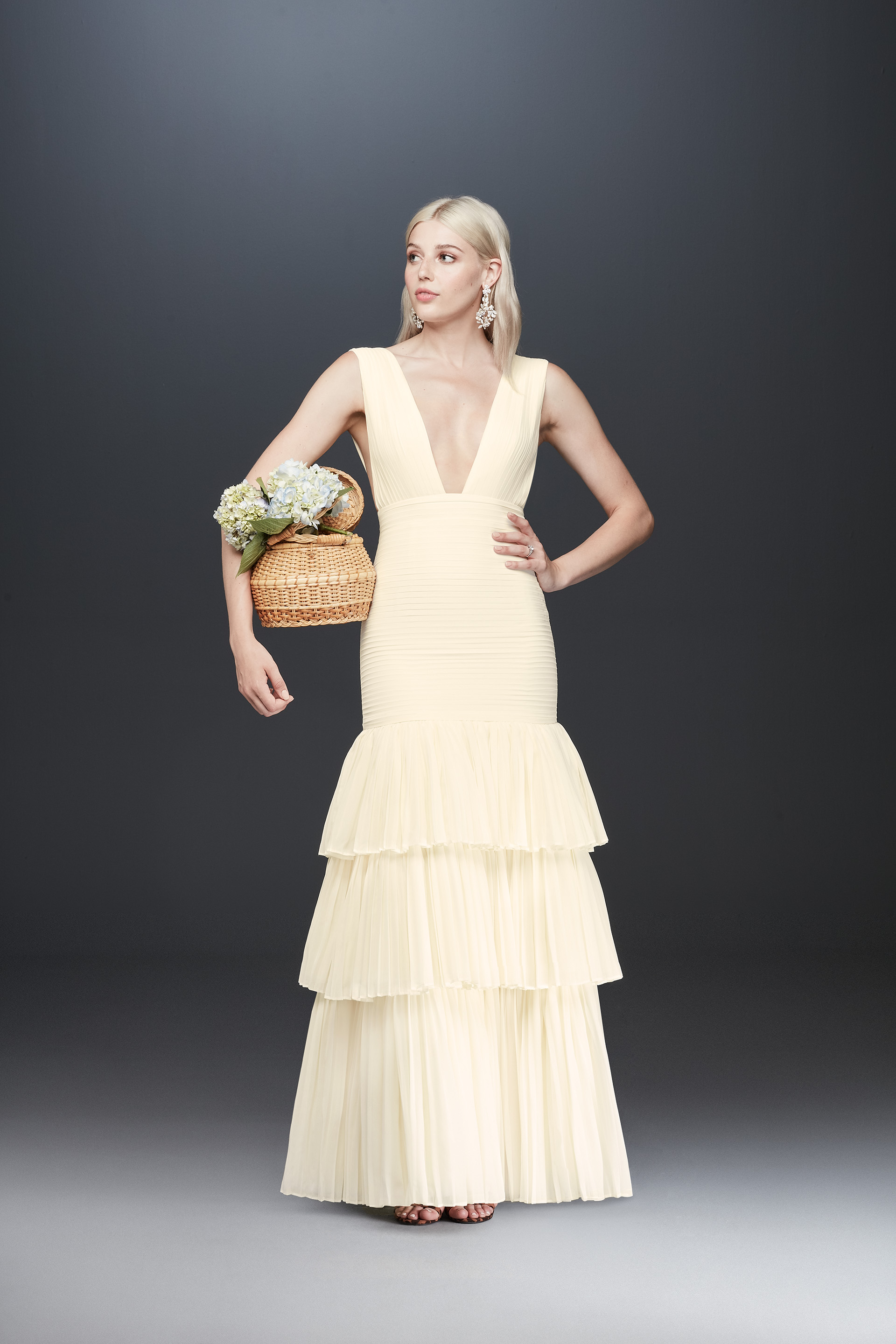 Bride holding woven basket wearing plunging neckline tiered long dress from Fame & Partners x David's Bridal collection