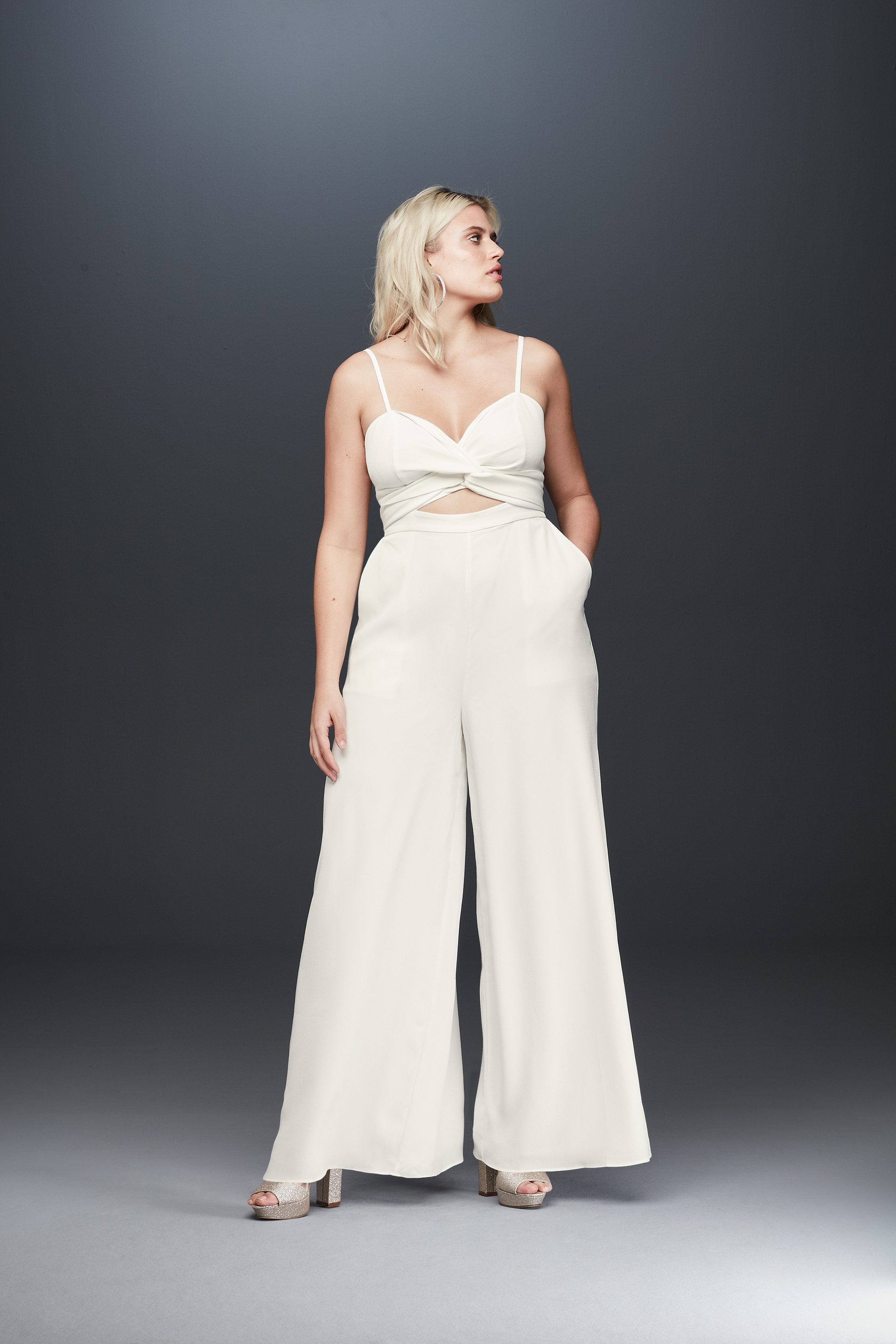 Bride looking away in spaghetti strap bridal jumpsuit from Fame & Partners x David's Bridal collection