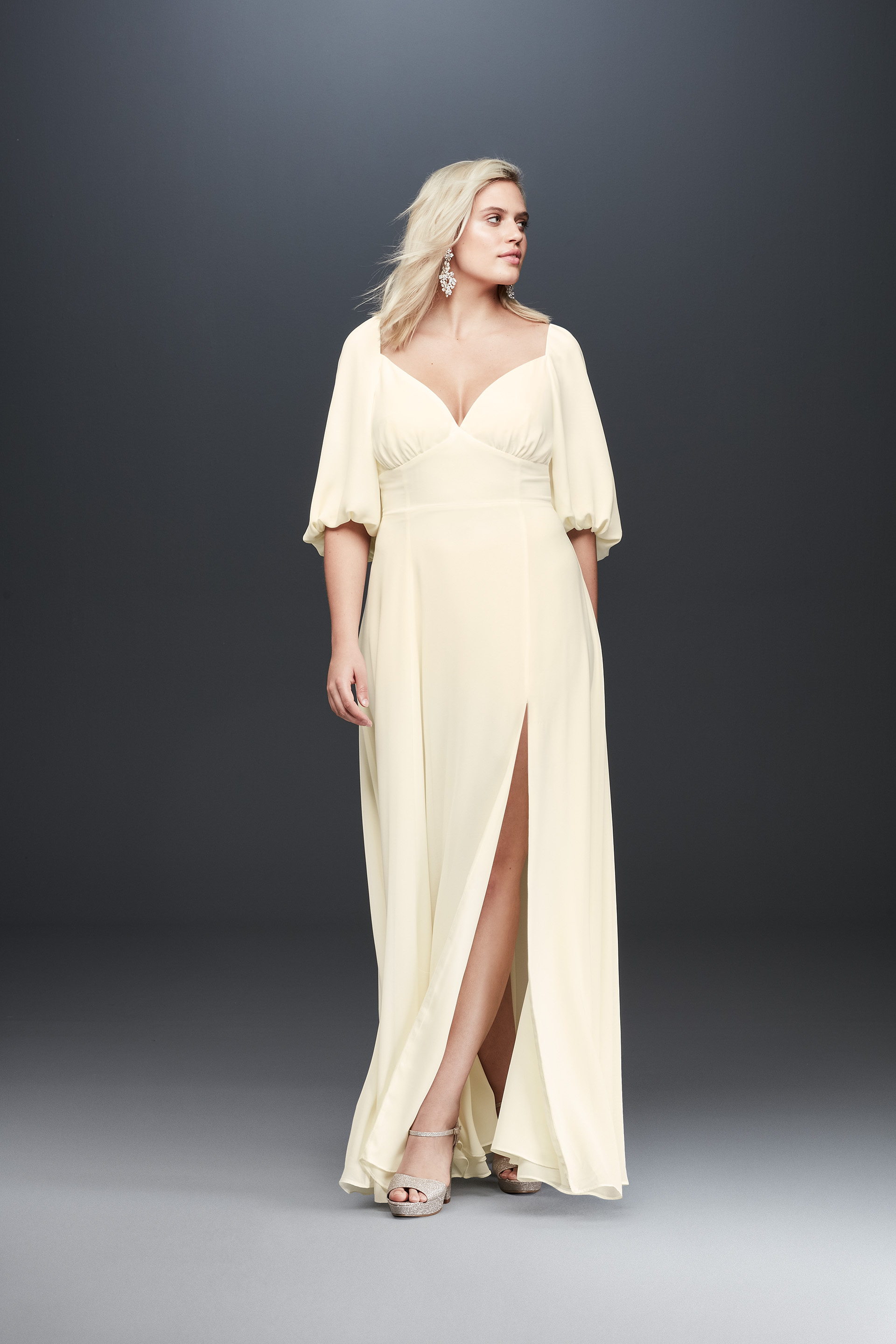 Bride looking away in peasant sleeve long wedding dress with slit from Fame & Partners x David's Bridal collection
