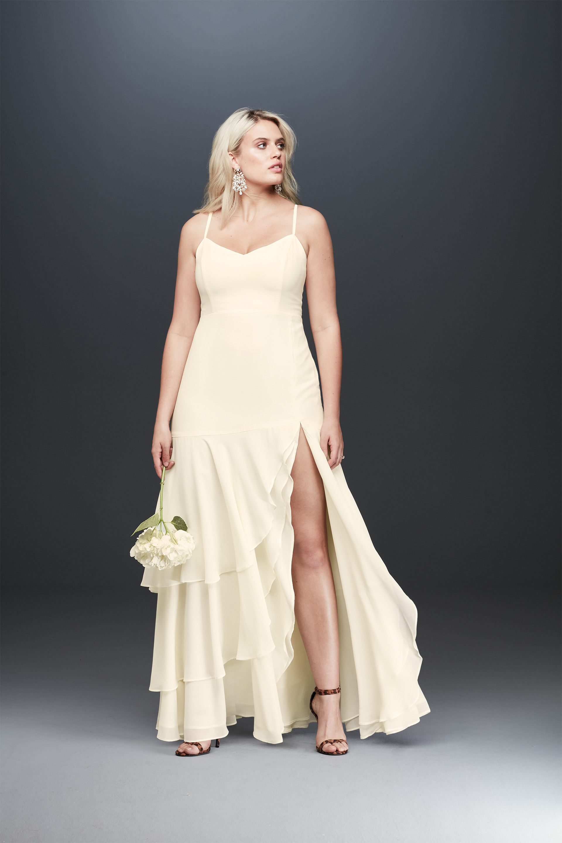 Bride looking away in spaghetti strap ruffled skirt wedding dress from Fame & Partners x David's Bridal collection