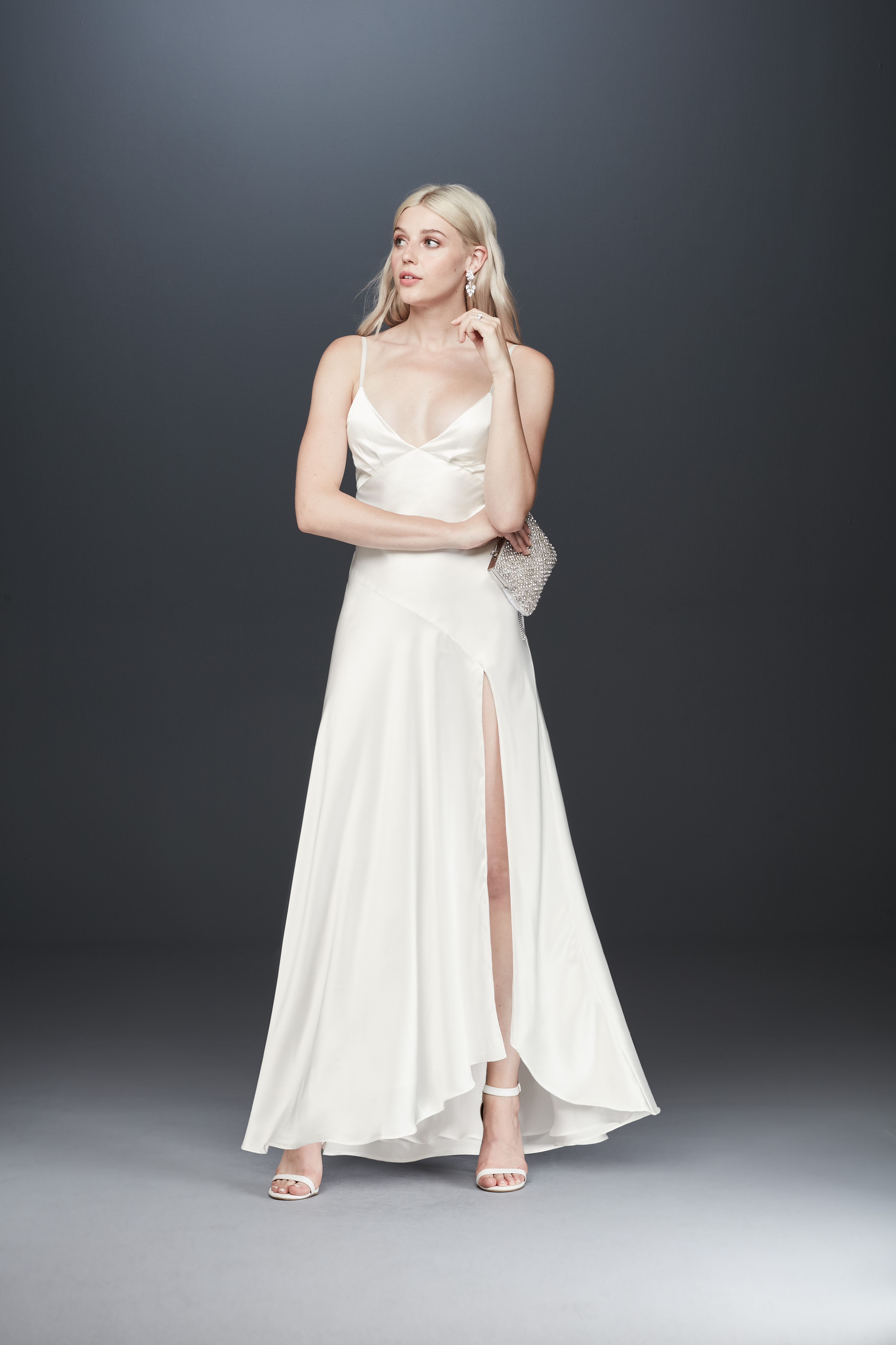 Bride looking away in spaghetti strap satin sheath wedding dress from Fame & Partners x David's Bridal collection