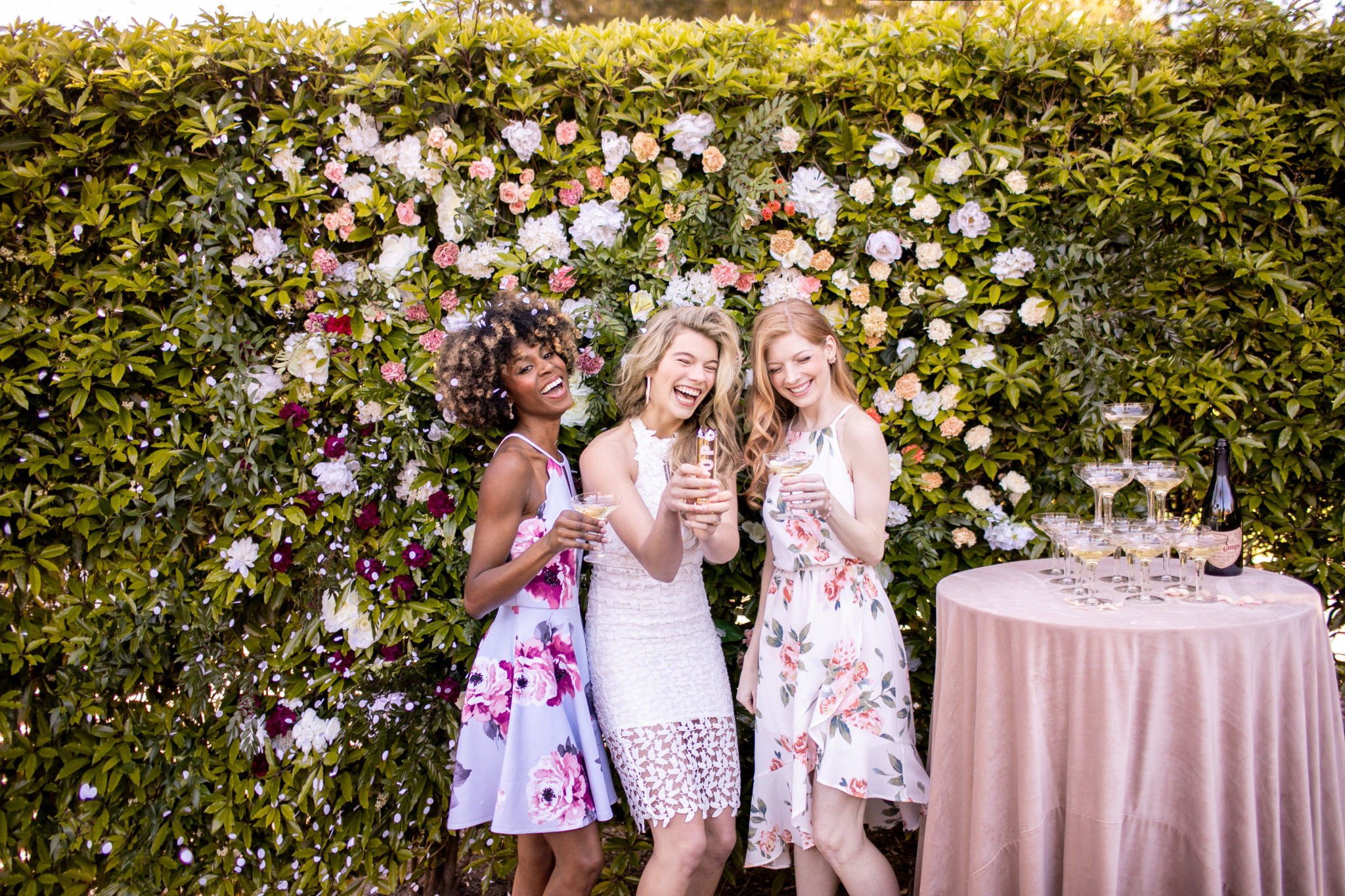 three young women in floral and white dresses toasting champagne