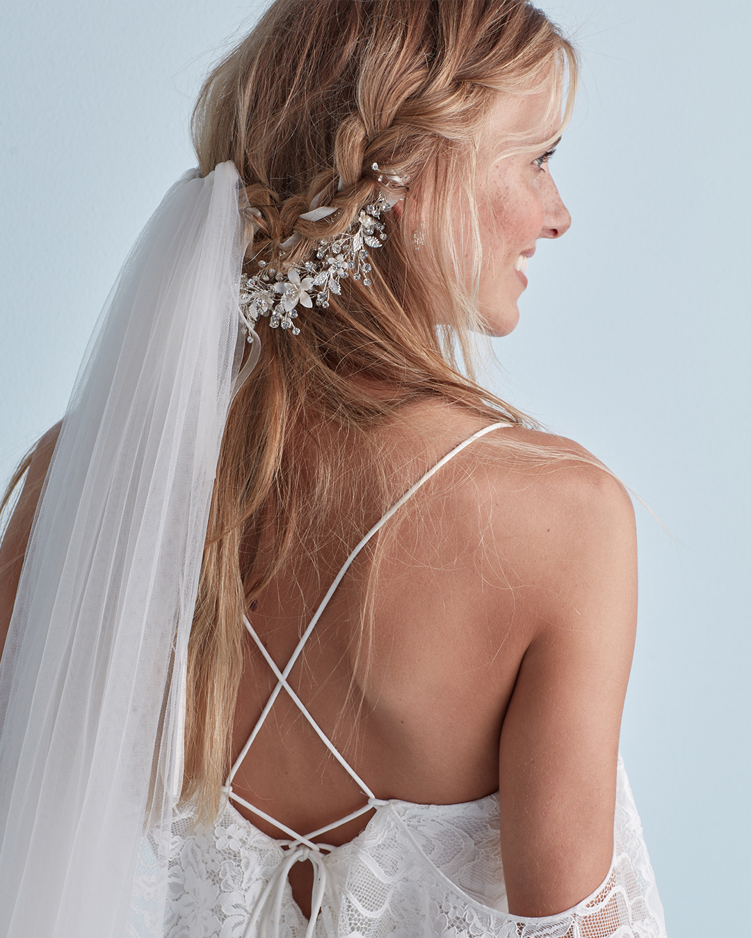 Wedding hairstyle with braid, crystal headband, and veil