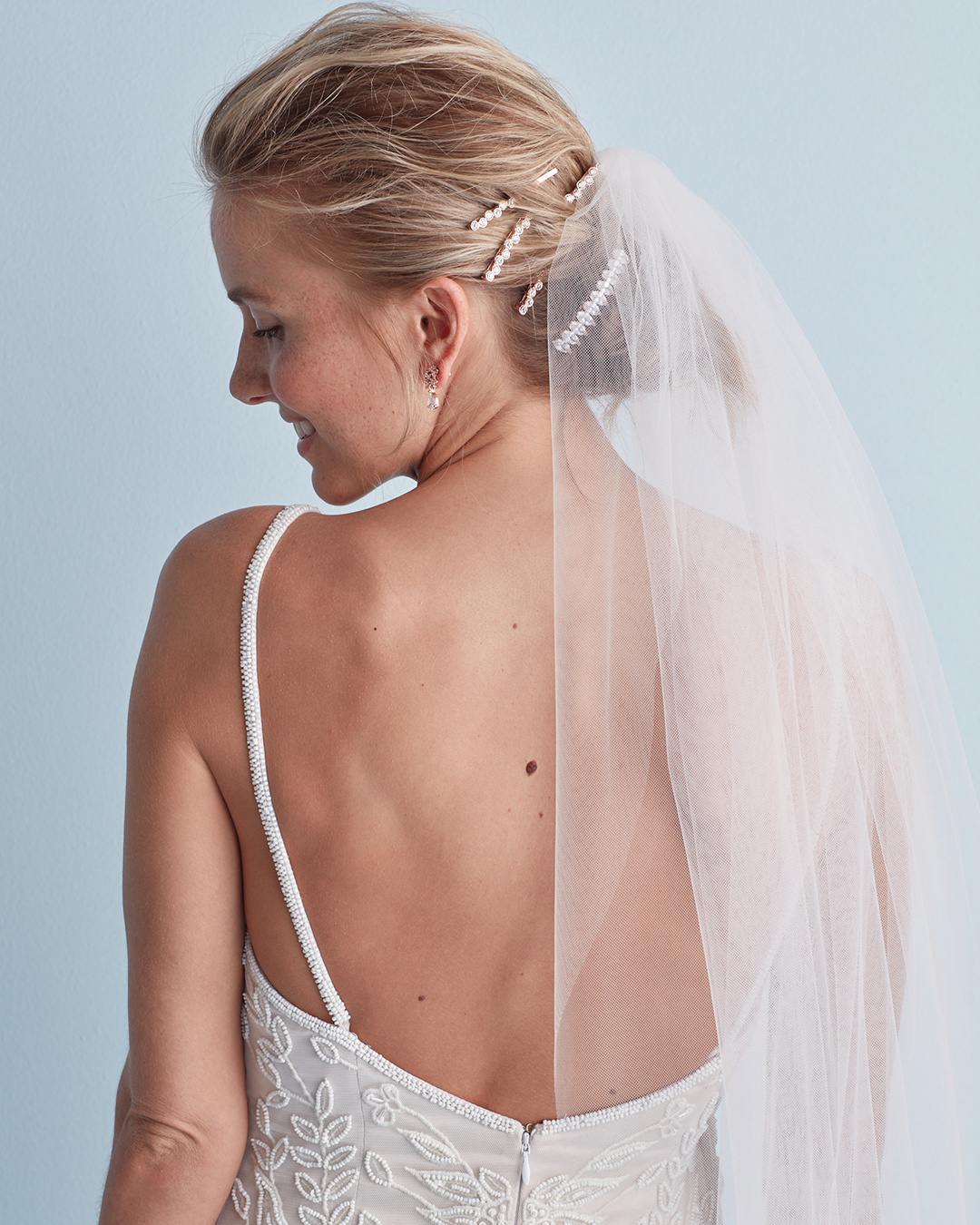 Wedding hairstyle with layered pins and veil in messy bun