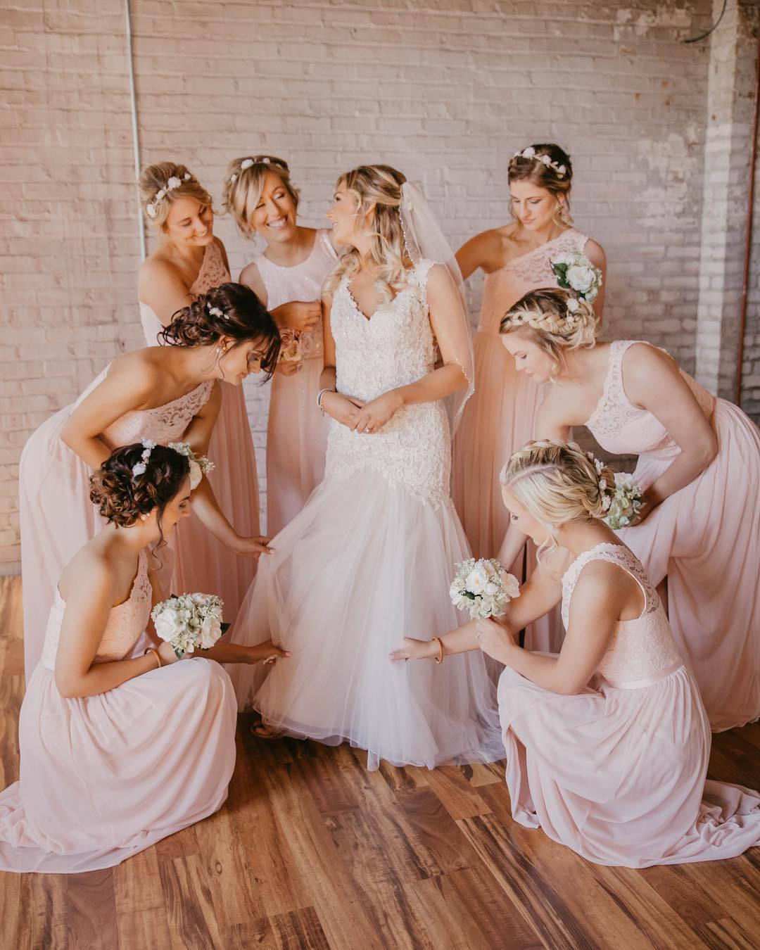 Bridesmaids helping bride get dresses