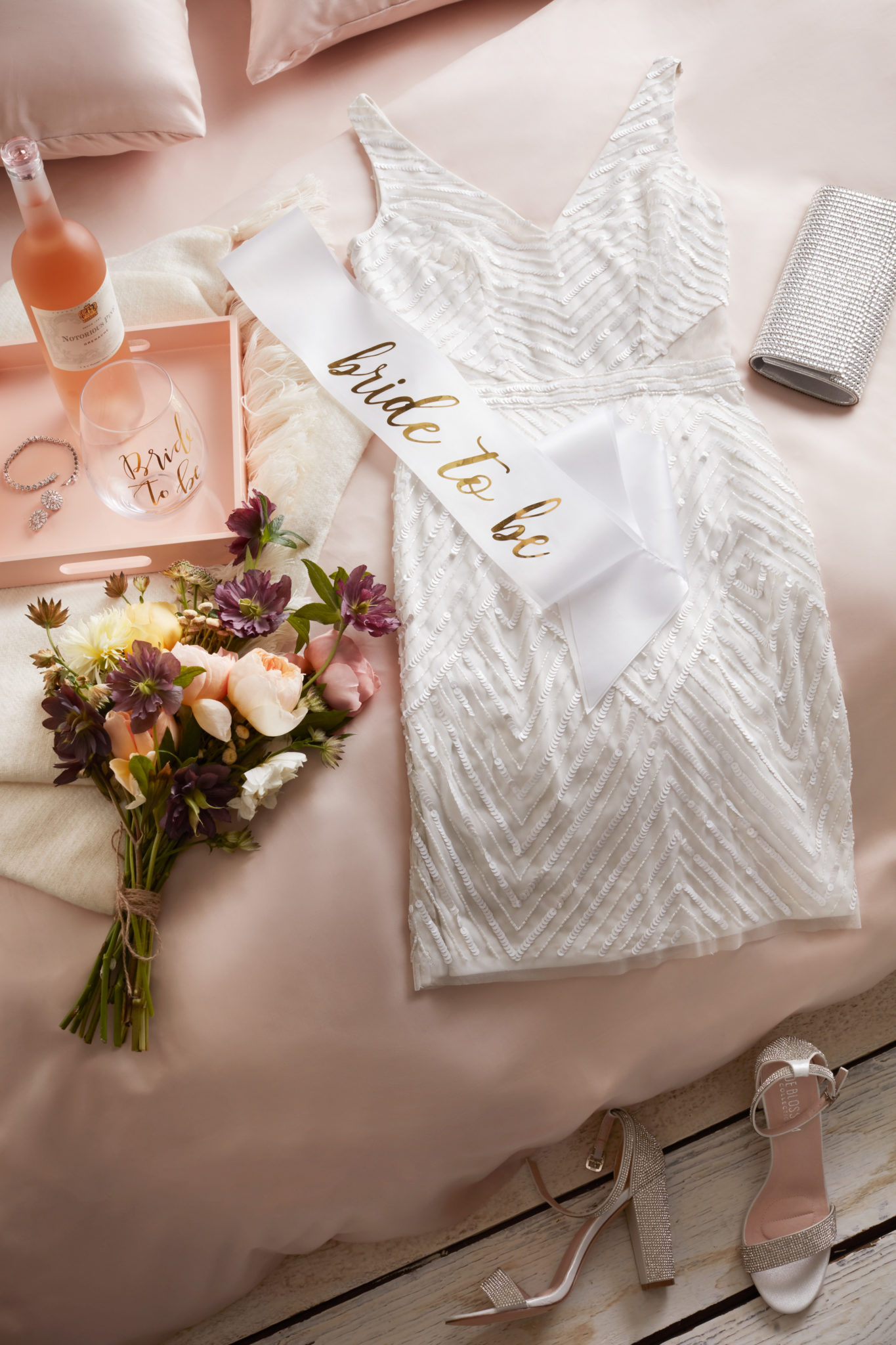 White dress laying on bed with flowers and tray of wine