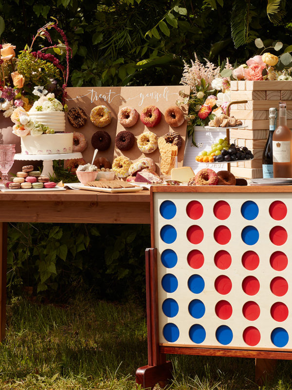 Outdoor reception table with cake, donuts, and oversized yard games
