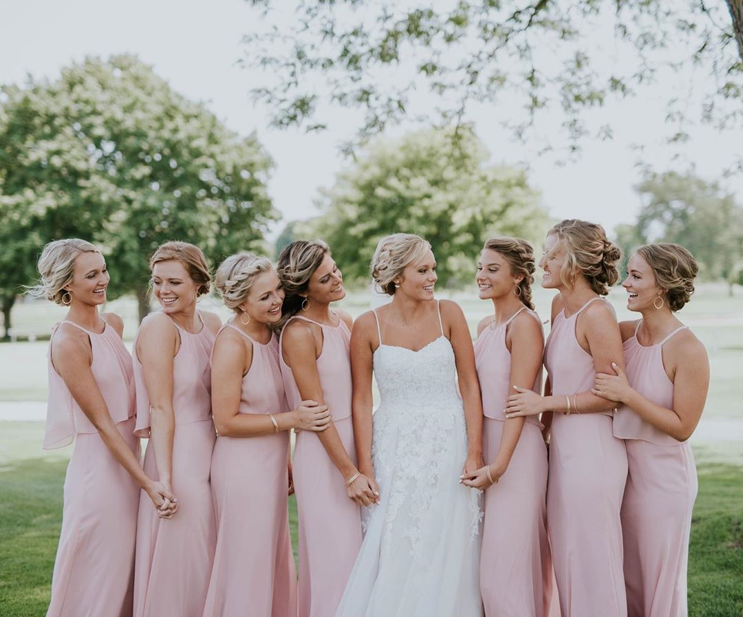 Bride and bridesmaids smiling and holding hands