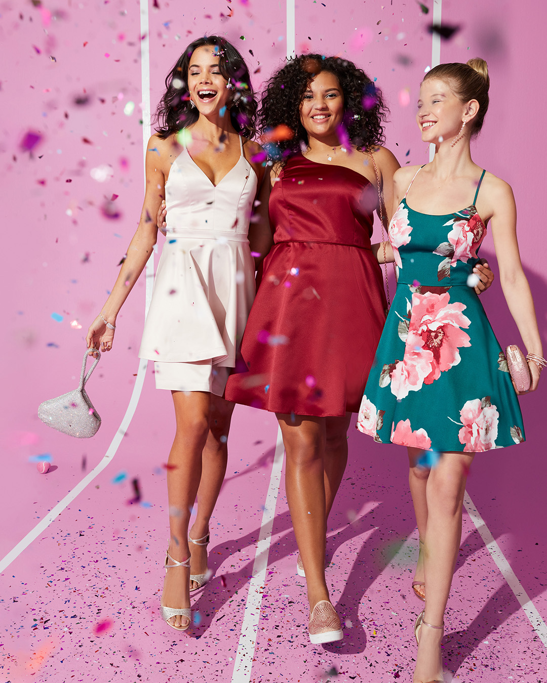 Girls arm-in-arm in short homecoming dresses with confetti