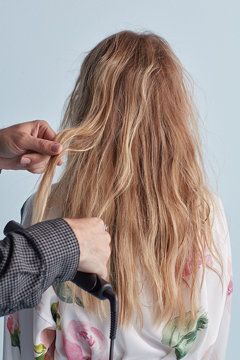 Hair stylist creating textured S waves with flat iron
