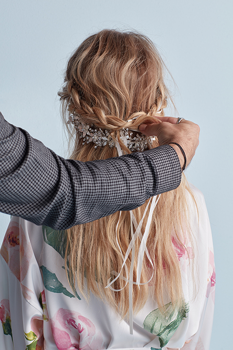 Hair stylist braiding ribbon into hair