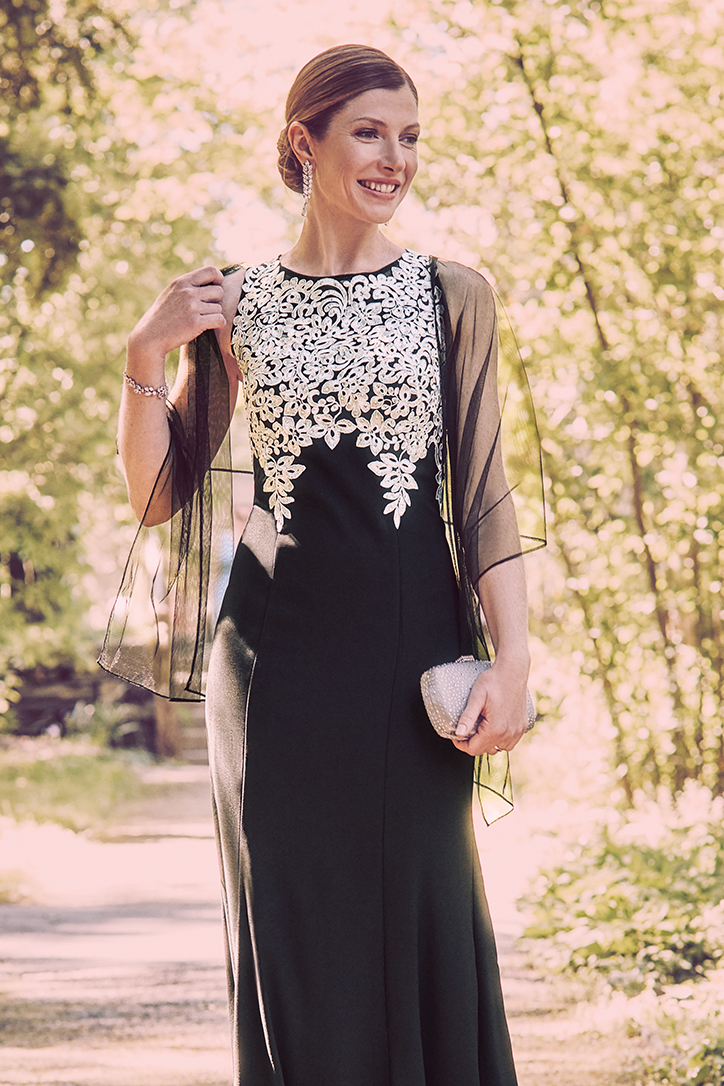 Woman in black high neck special occasion dress with embroidery