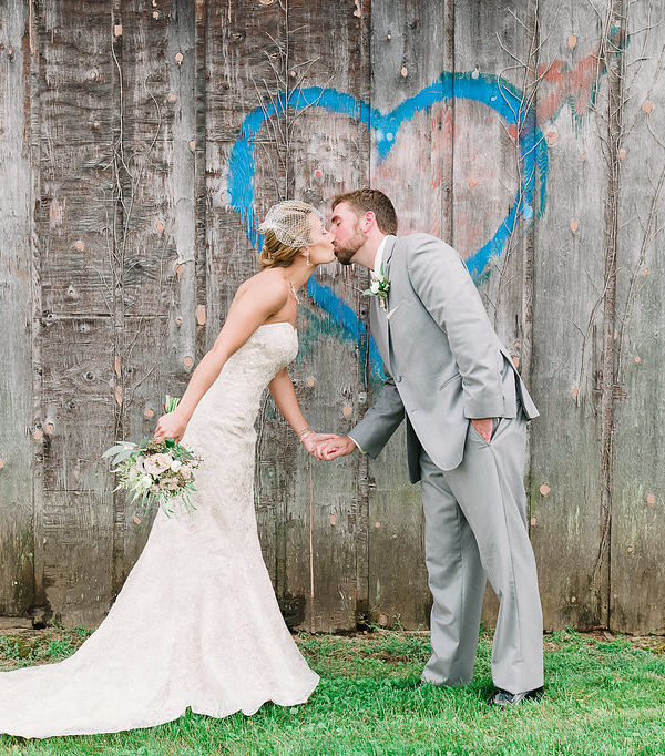 Bride and Groom kiss in front of blue heart