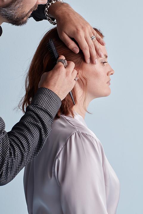 Hair stylist combing hair