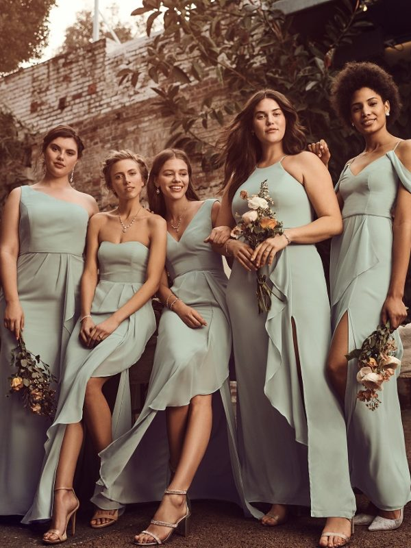 Group of bridesmaids in long green dresses with differnt style tops