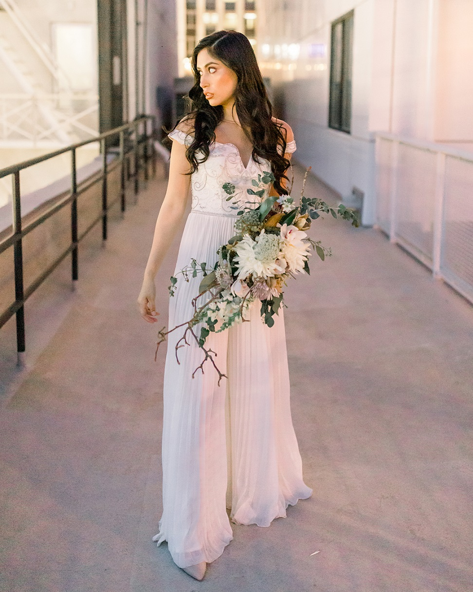 Bride in bridal jumpsuit with bouquet