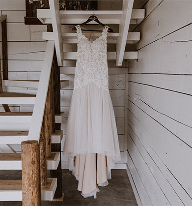 Wedding dress hanging from white washed staircase