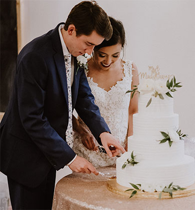 Bride and groom cutting a four-tier wedding cake.