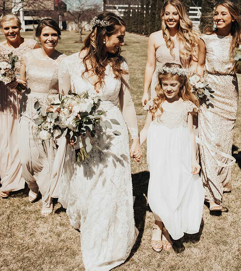 Bride holding hands with flower girl with bridesmaids in beige and gold dresses behind them
