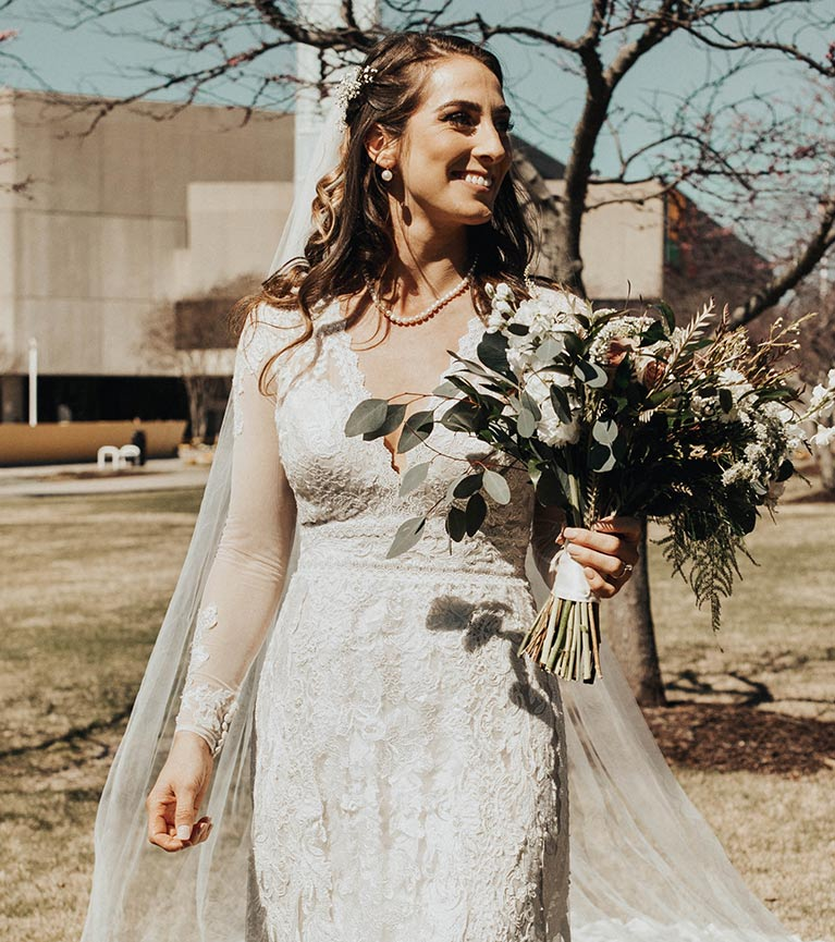 Bride in long sleeve lace wedding dress with a bridal bouquet filled with lush greenery and white flowers.