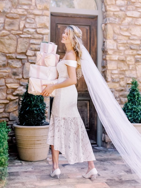Bride in short lace dress and long veil carrying gifts
