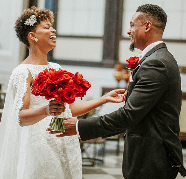 Bride Holding Red Bouquet Looking at Groom