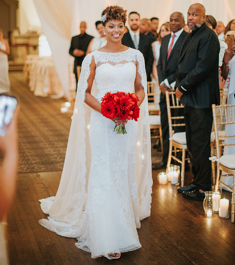 Bride  walking down the aisle with a red floral bouquet