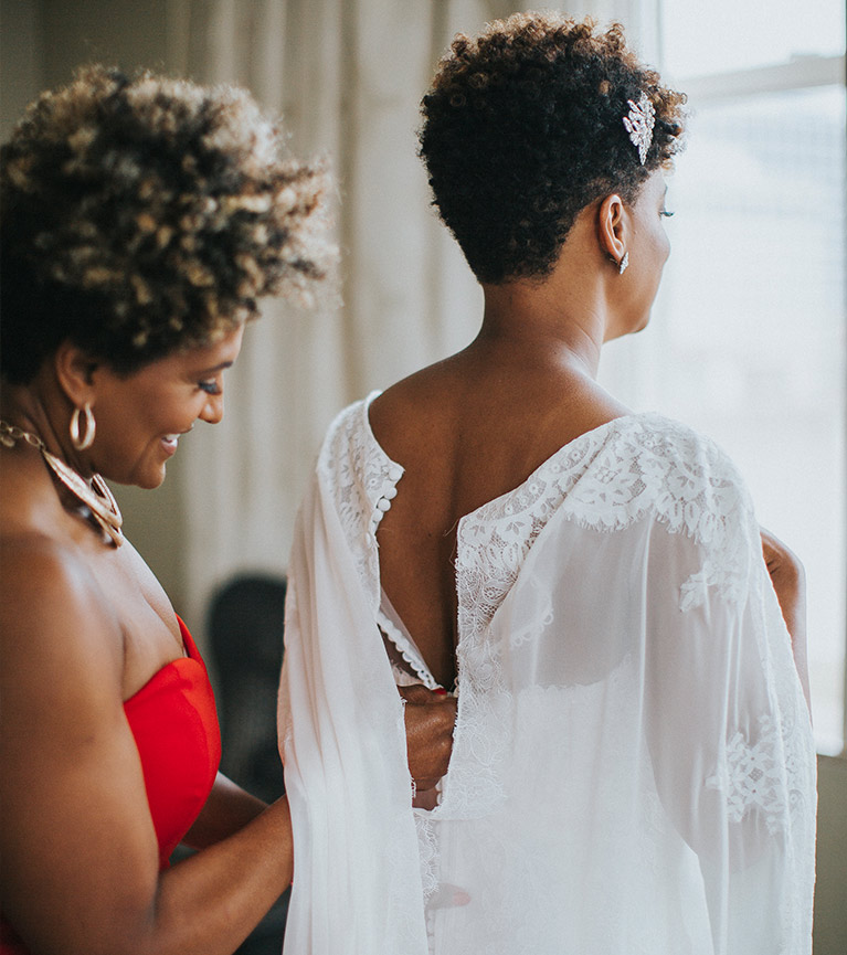 Mother of the bride helping her daughter button the back of her wedding dress