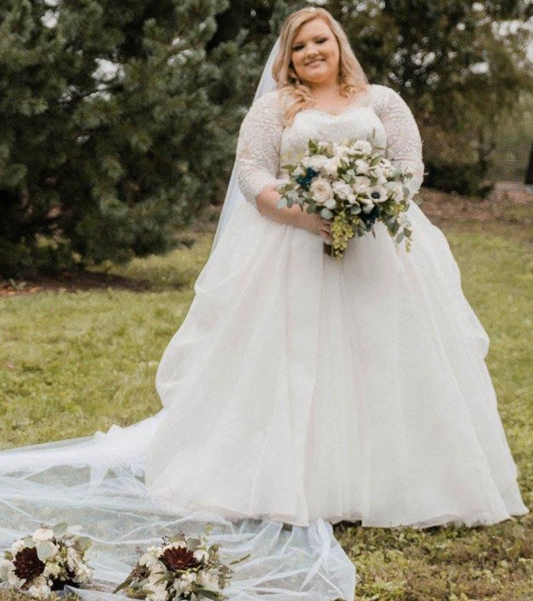 Bride in long sleeve lace ballgown holding a bouquet of white flowers with dark flowers mixed in.