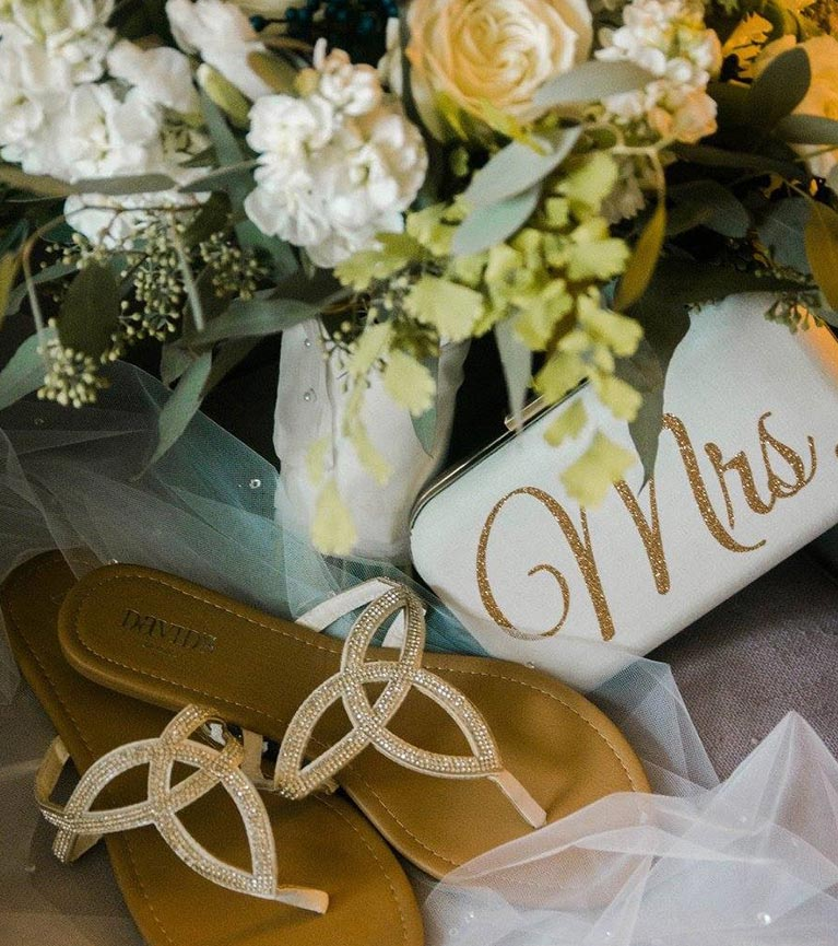 "Bridal bouquet, ivory clutch with ""Mrs"" in gold glitter, and gold and crystal sandals on top of a crystal adorned veil."
