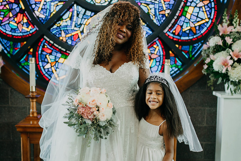 Bride with daughter in a white dress, tiara and short veil in front of a stained glass window
