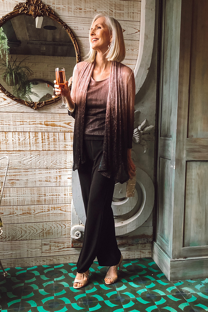 Woman in a special occasion pantsuit holding champagne glass